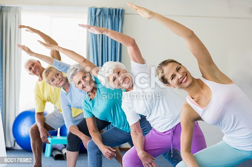 600177016 istock photo Instructor performing yoga with seniors 600176982