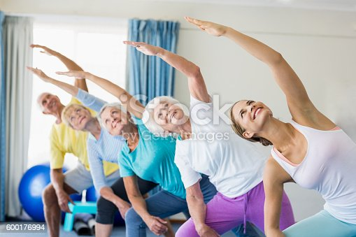 600177016 istock photo Instructor performing yoga with seniors 600176994