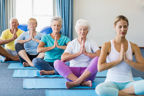 instructor performing yoga with seniors - yoga stock photos and pictures