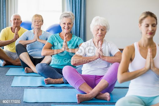 600177016 istock photo Instructor performing yoga with seniors 600177020