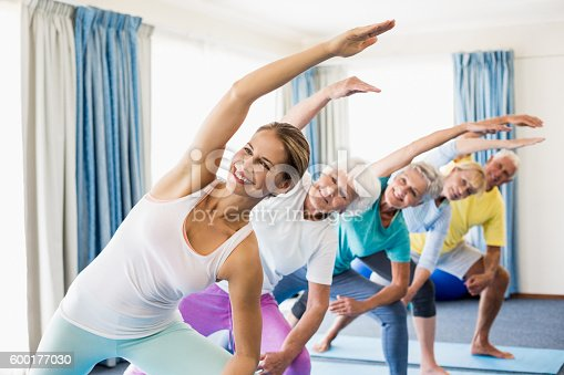 600177016 istock photo Instructor performing yoga with seniors 600177030