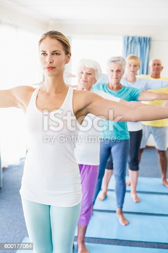 600177016 istock photo Instructor performing yoga with seniors 600177084