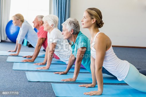 600177016 istock photo Instructor performing yoga with seniors 600177110