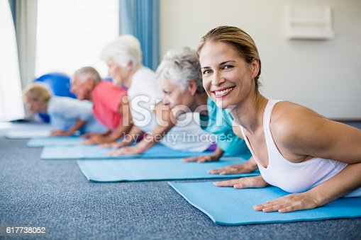 600177016 istock photo Instructor performing yoga with seniors 617738052