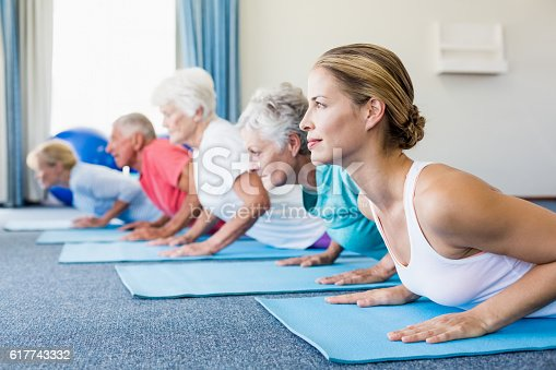 600177016 istock photo Instructor performing yoga with seniors 617743332
