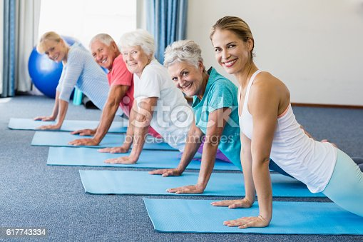 600177016 istock photo Instructor performing yoga with seniors 617743334