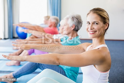 600177016 istock photo Instructor performing yoga with seniors 617743366