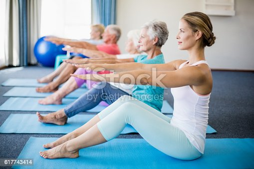 600177016 istock photo Instructor performing yoga with seniors 617743414