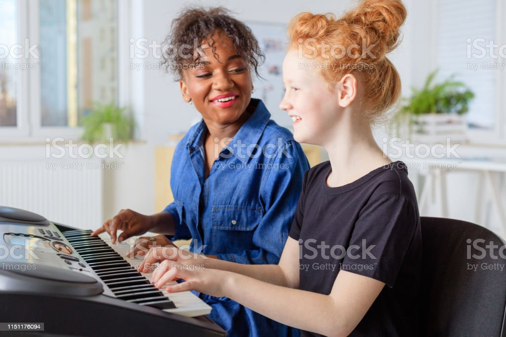 Instructor singing while teaching piano in class Smiling female instructor singing while teaching piano to student. Pre-adolescent girl is learning keyboard instrument. They are sitting in training class at conservatory. 12-13 Years Stock Photo