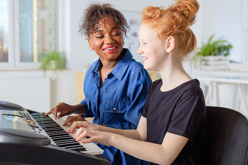 Instructor Singing While Teaching Piano In Class Stock Photo - Download Image Now