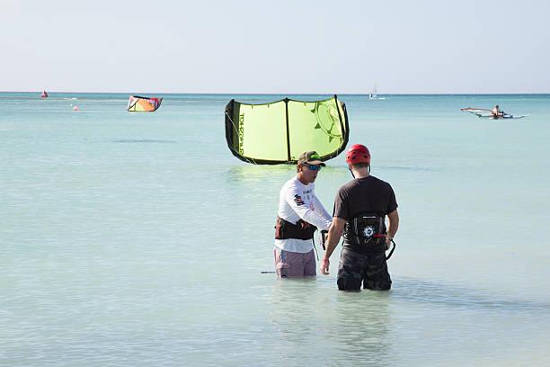 trainer hilft ein schüler zu kiteboard - kitesurfen lernen stock-fotos und bilder