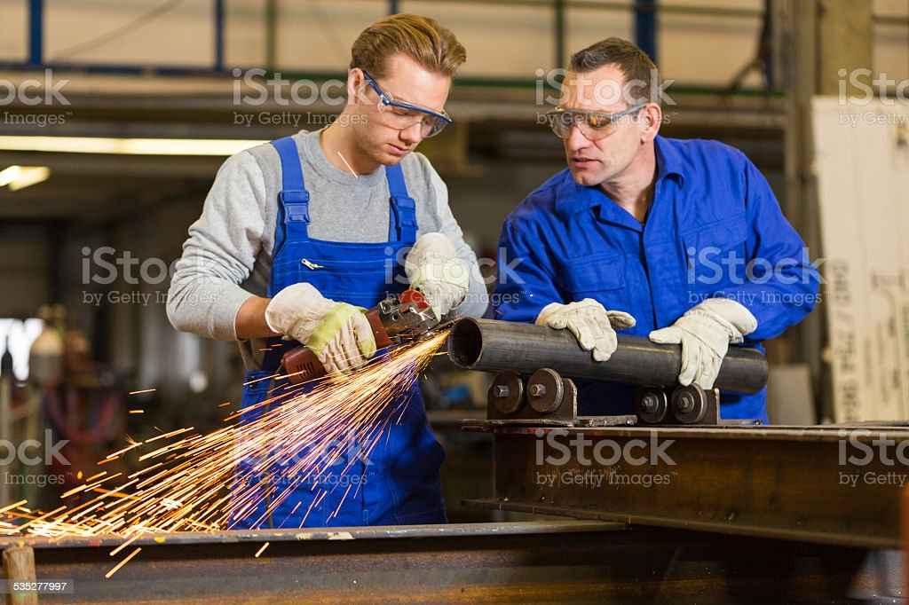 instructor teaches trainee how to use an angle grinder stock photo