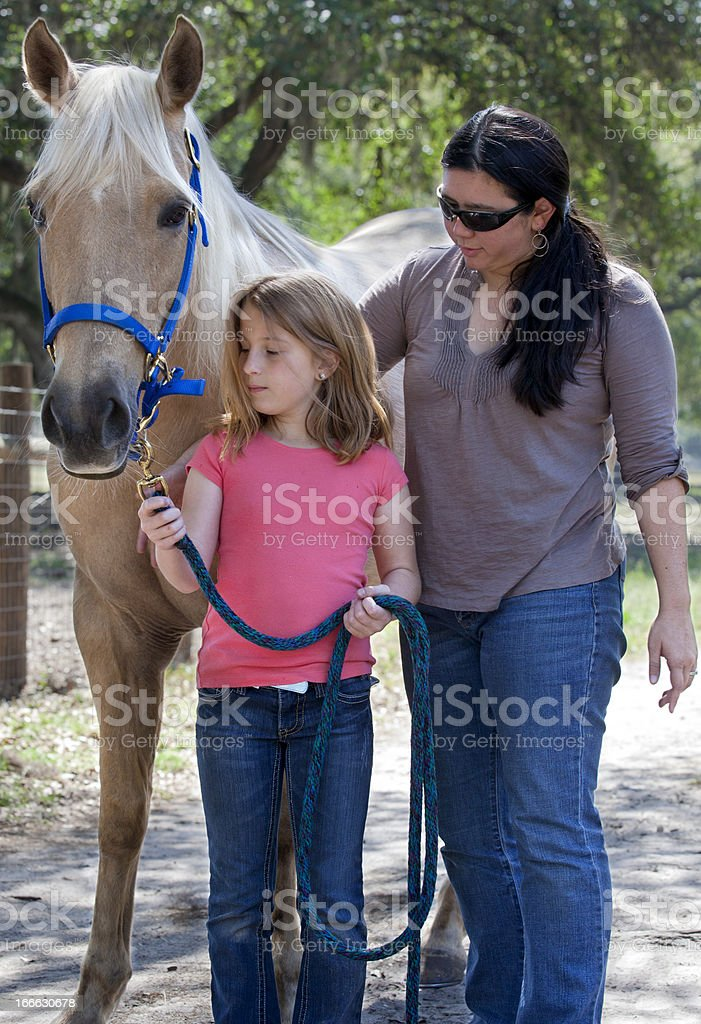 Instructor Teaching a Young Girl about Horse royalty-free stock photo