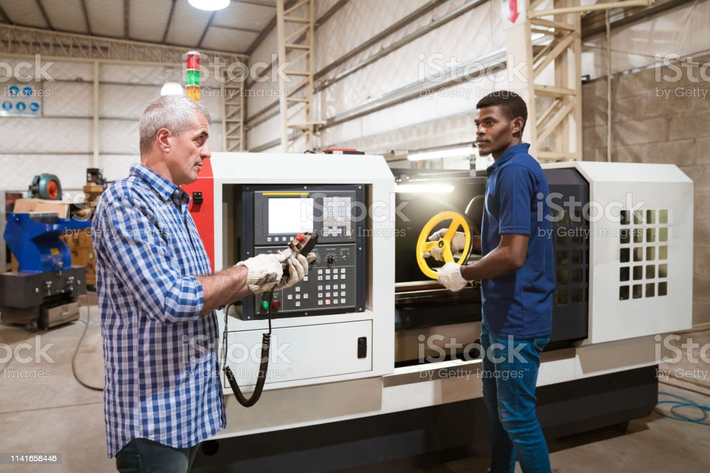 Instructor teaching apprentice in factory Mature instructor teaching apprentice in factory. Male trainee holding wheel is while engineer using remote control. They are working in industry. 25-29 Years Stock Photo