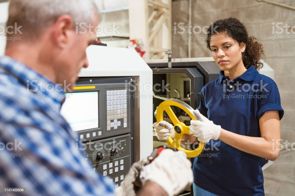 Instructor teaching apprentice in industry Mature instructor teaching female apprentice in factory. Trainee holding wheel is looking at engineer using remote control. They are in industry. 30-34 Years Stock Photo