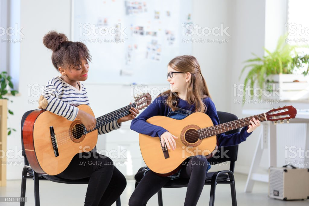 Instructor teaching girl plucking guitar at class Female instructor teaching girl plucking guitar at classroom. Pre-adolescent student is practicing string instrument at conservatory. They are sitting in training class. 10-11 Years Stock Photo