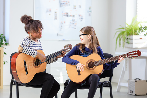 Instructor Teaching Girl Plucking Guitar At Class Stock Photo - Download Image Now