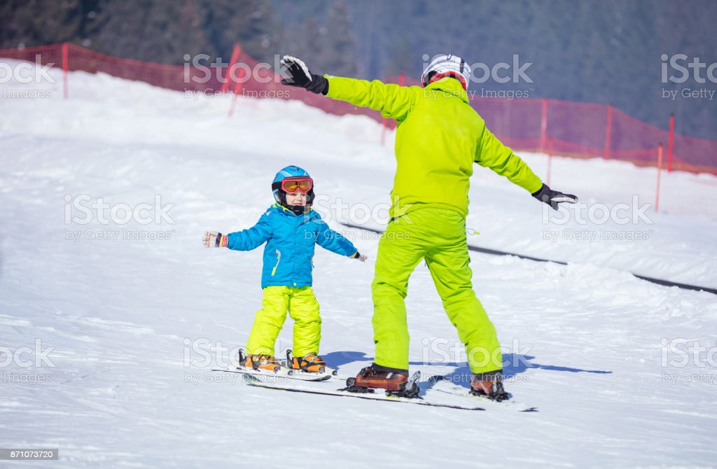 Instructor teaching little boy to ski stock photo