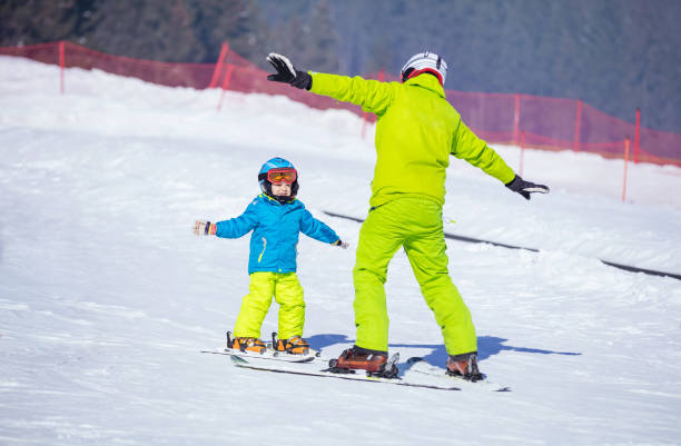 Instructor teaching little boy to ski stock photo