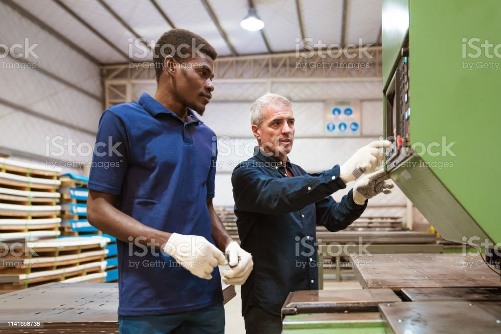 Instructor teaching male trainee in factory Mature engineer explaining apprentice over manufacturing machinery. Instructor is discussing with trainee in factory. They are standing in industry. 25-29 Years Stock Photo