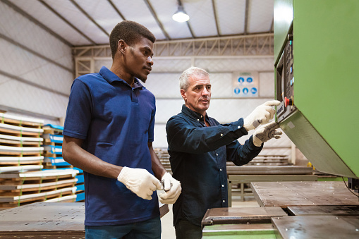 Instructor Teaching Male Trainee In Factory Stock Photo - Download Image Now