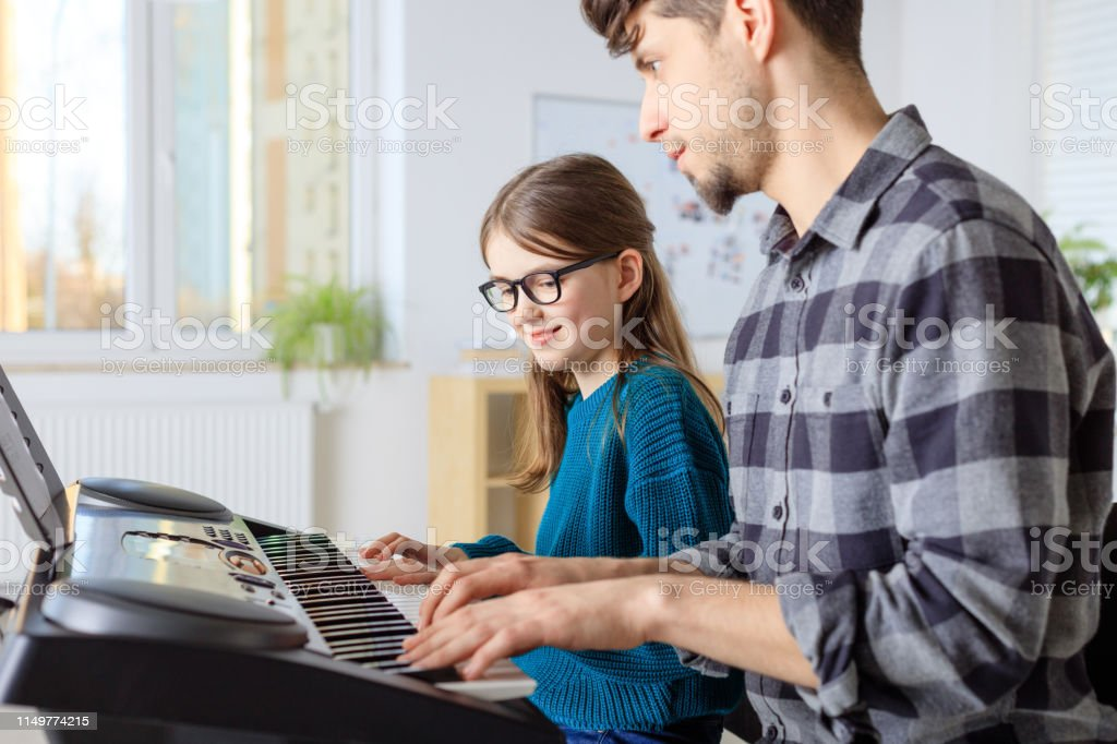 Instructor teaching piano to girl in class Smiling teacher teaching piano to female student. Pre-adolescent girl is learning music in class. They are practicing in casuals at conservatory. 10-11 Years Stock Photo