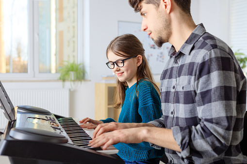 Instructor Teaching Piano To Girl In Class Stock Photo - Download Image Now