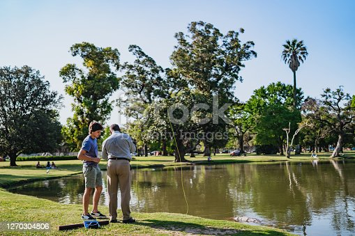 Instructor teaching his pupil fishing in lake in public park on sunny day.