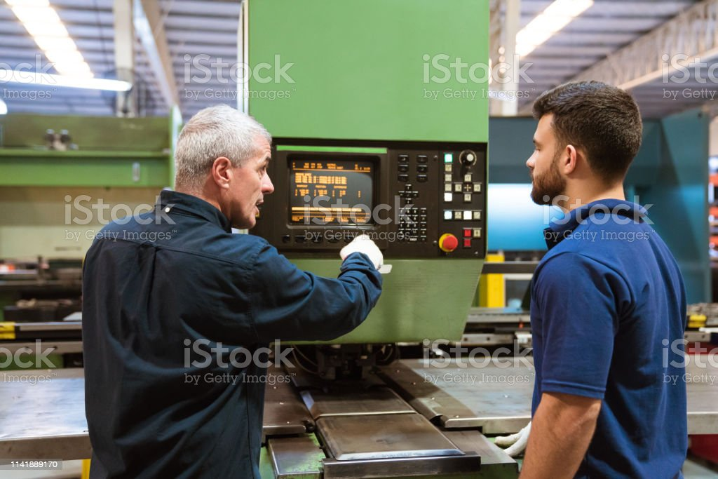 Instructor teaching trainee in factory Mature engineer explaining trainee over puller machine. Instructor is teaching apprentice in factory. They are standing in industry. 20-24 Years Stock Photo