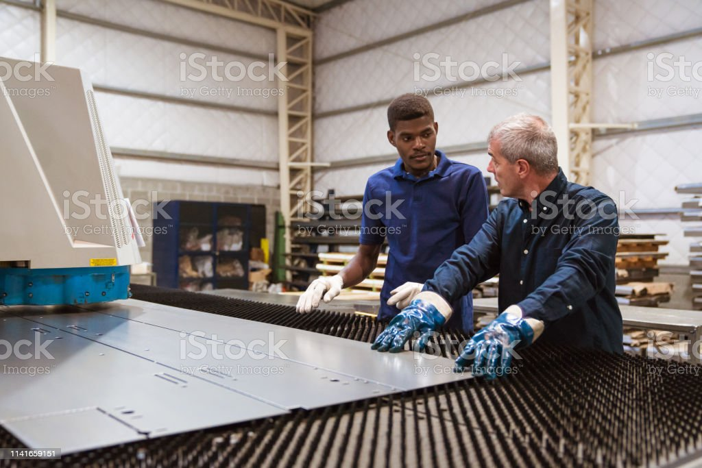 Instructor teaching trainee in industry Male instructor teaching trainee in industry. Engineer is discussing with apprentice over puller machine. They are working in factory. 25-29 Years Stock Photo