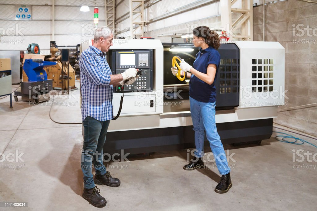 Instructor teaching training in factory Male engineer teaching female trainee in industry. Apprentice holding wheel is looking at engineer using remote control. They are in factory. 30-34 Years Stock Photo