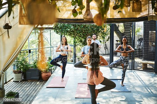 Rear view of instructor teaching tree pose to clients on porch. Multi-ethnic people practicing yoga on mat. They are in sports clothing.