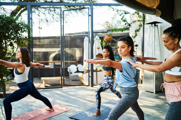 Instructor teaching warrior position on porch Mid adult female instructor teaching warrior position. Multi-ethnic women are practicing yoga at porch. They are in sports clothing. yoga instructor stock pictures, royalty-free photos & images