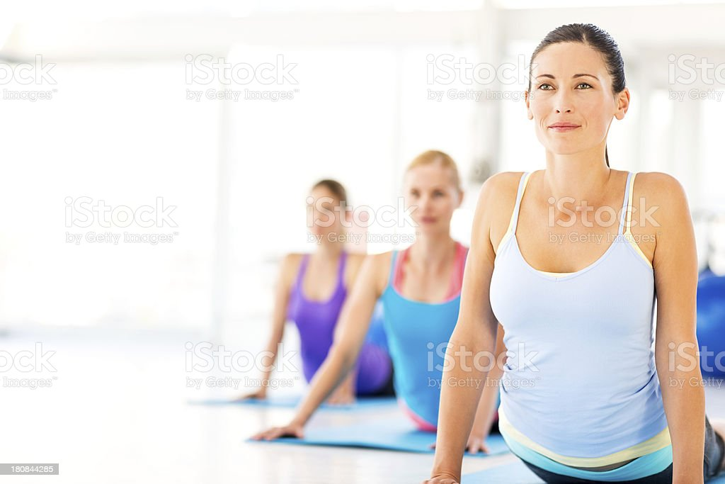 Instructor With Class Practicing Yoga Exercise In Gym stock photo