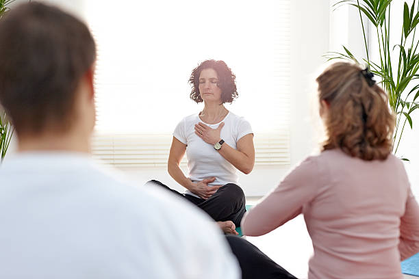 Instructor with group of people in yoga class Instructor with group of people in yoga class exercising yoga instructor stock pictures, royalty-free photos & images