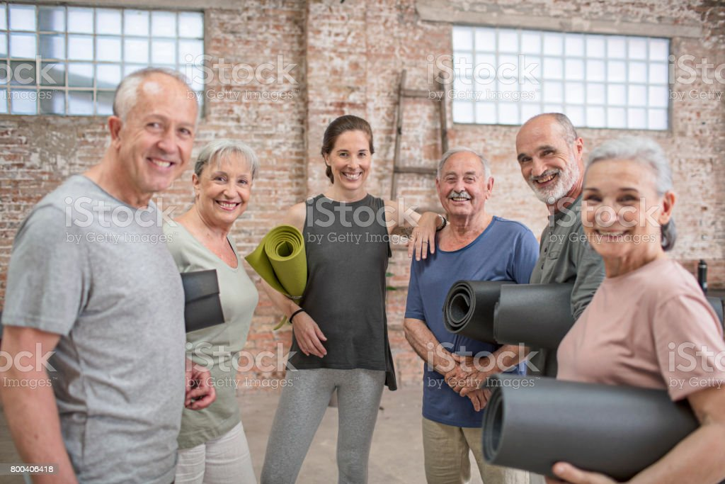 Instructor with happy senior people in yoga class stock photo