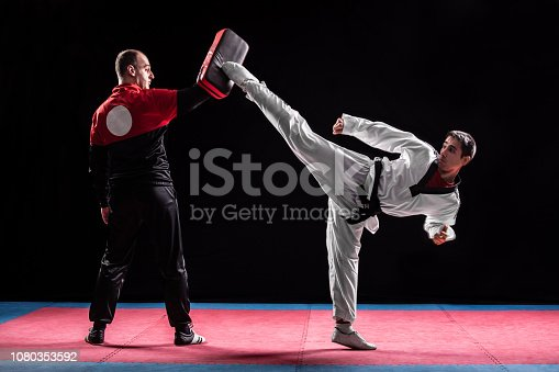 Sports trainer assisting to man competitor in taekwondo. Taekwondo is one of the most popular martial arts. Theay are working in gym with dark background