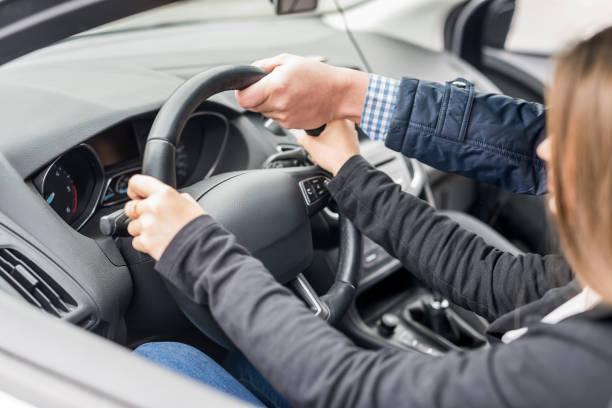 mano del instructor ayudando a dirigir a una mujer - aprender a conducir fotografías e imágenes de stock