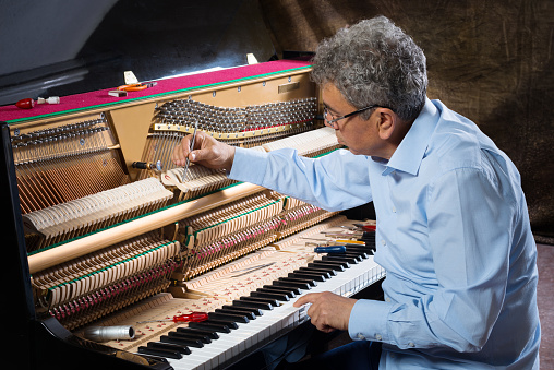 Instrument technician tuning a piano.