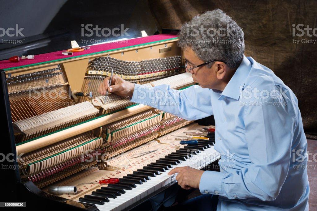 Instrument technician tuning piano stock photo
