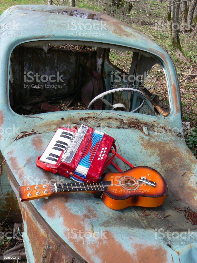 Instruments de musique d'enfant sur une épave de voiture - foto de stock