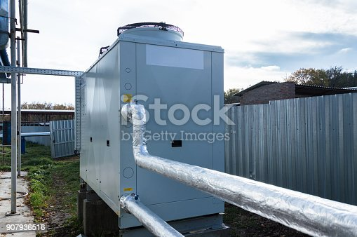 istock Insulated pipelines connecteed to the gray commercial chiller standing outdoor on the ground near to the modern fabrication building 907936516