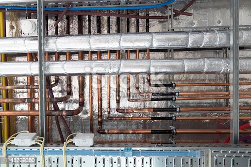 insulates hot water pipes and copper pipes hang from the subceiling on an unfinished construction site
