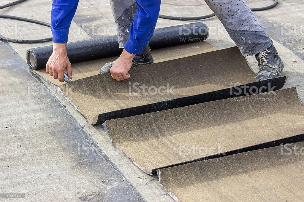 Insulation worker cutting insulation bitumen material rolls stock photo
