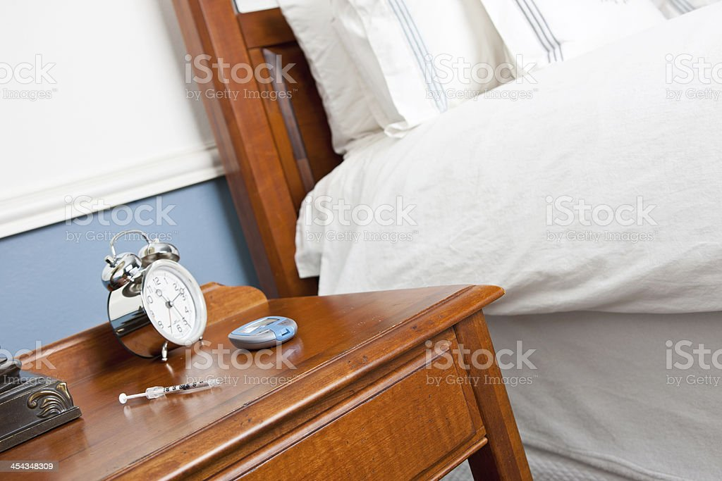 Insulin Needle and Glucometer on Night Stand royalty-free stock photo