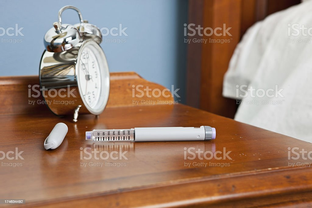 Insulin Pen and Glucometer on Night Stand stock photo