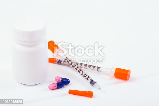 istock Insulin syringes, two capsules and plastic bottle on white background. 1092248526
