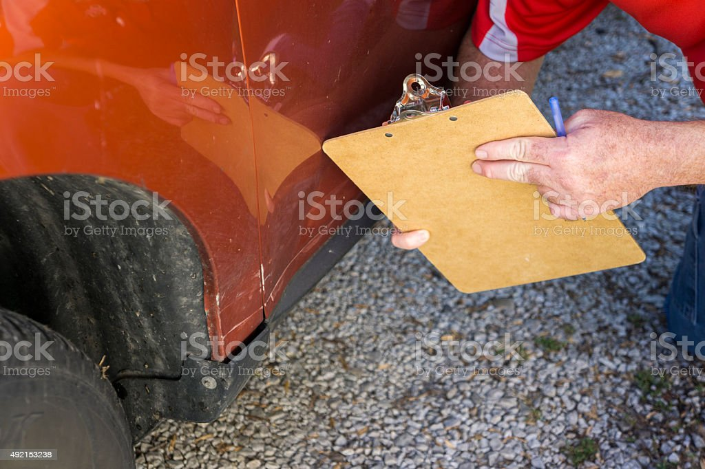 Insurance Adjuster Examing Damages stock photo