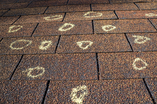 Insurance adjuster marked the hail damage on a insureds roof.