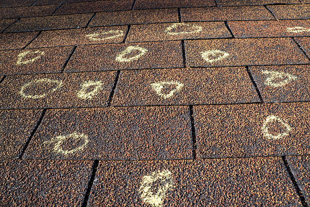 insurance adjuster marked roof with hail damage - damaged stock photos and pictures